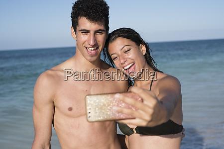 happy young couple taking selfies on