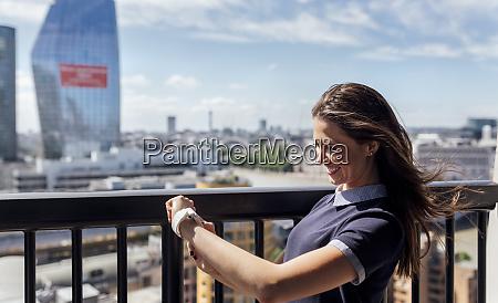 uk london happy woman using smartwatch