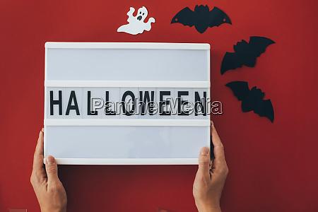 frau haelt halloween zeichen