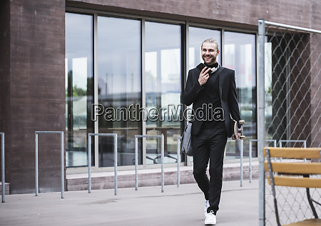 smiling fashionable young man holding cell