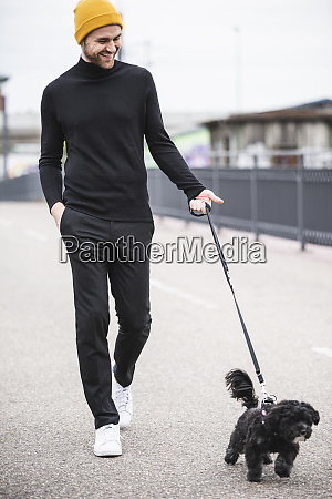 fashionable young man walking with dog