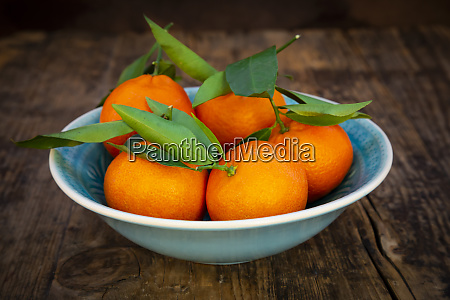 clementines in bowl on wood