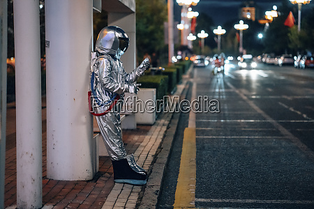 spaceman standing at a bus stop