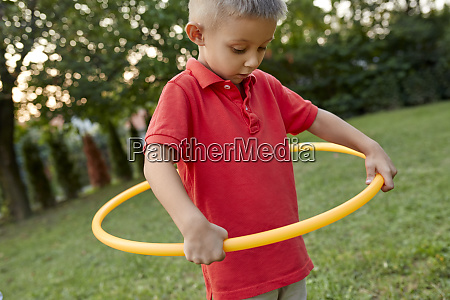 boy playing with hula hoop in