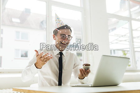 laughing businessman with laptop celebrating birthday