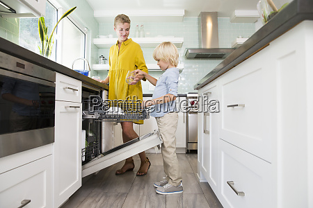 boy helping mother clearing the dishwasher