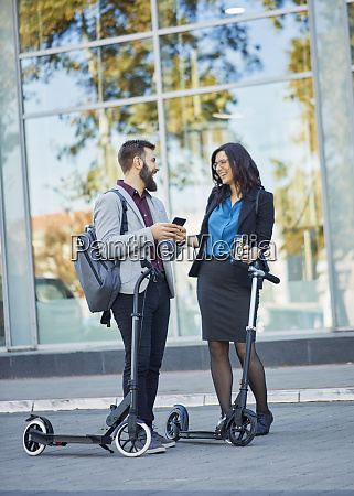 happy businessman and businesswoman with scooters