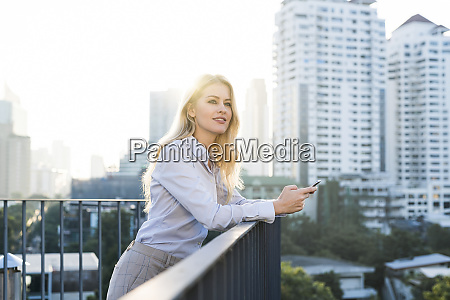 blonde smiling business woman leaning onto