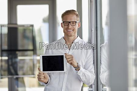 portrait of smiling businessman showing tablet