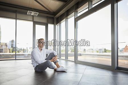 businessman sitting in empty room looking