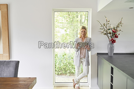 smiling woman standing at french door