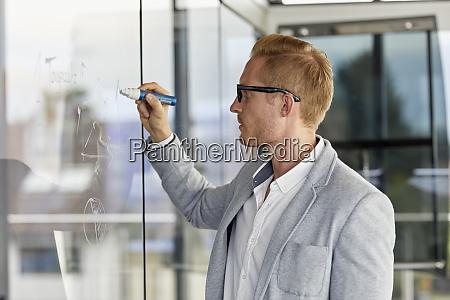geschaeftsmann schreibt auf glasscheibe im buero