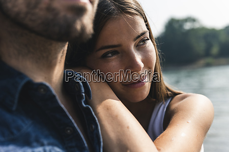 smiling young woman leaning against mans