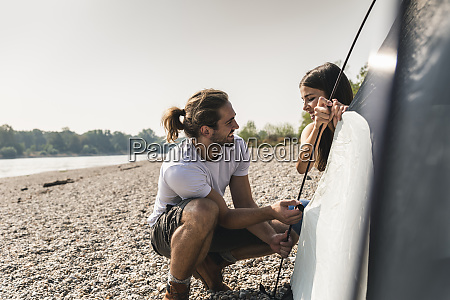 smiling young couple setting up a