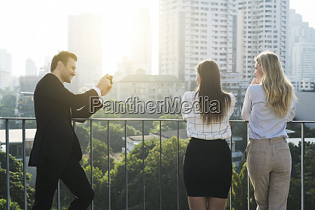 businessman taking picture of his female