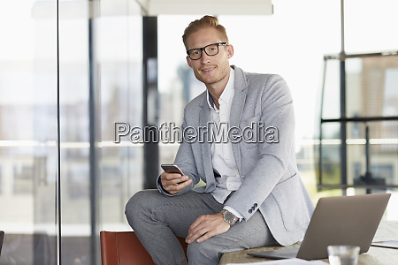 portrait of smiling businessman with laptop