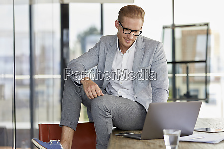 smiling businessman sitting on desk in