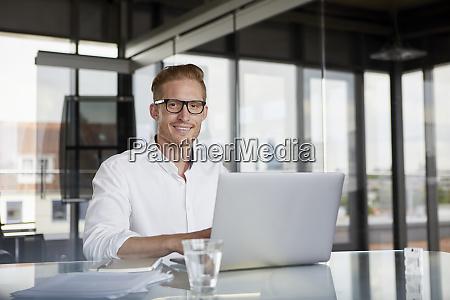 portrait of smiling businessman using laptop