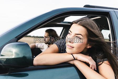 laechelnde junge frau die aus autofenster