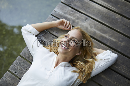 smiling blond woman lying on wooden