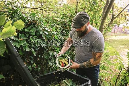 reifen mann entsorgt kuechenreste auf kompostpfahl