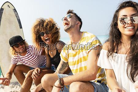 friends sitting on the beach having