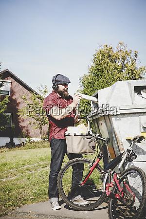 radfahrer recycelt altpapier in papierbank