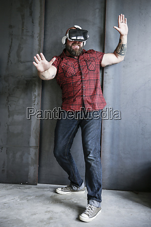 excited bearded man wearing vr glasses