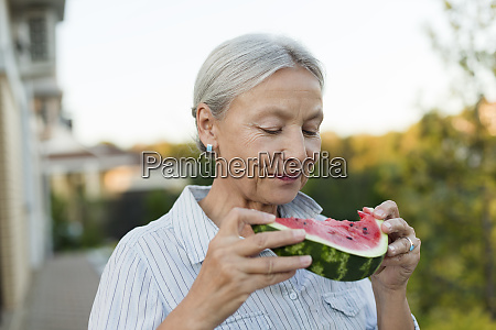 portrait of senior woman eating watermelon