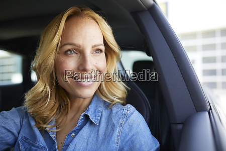 portrait of smiling woman driving car