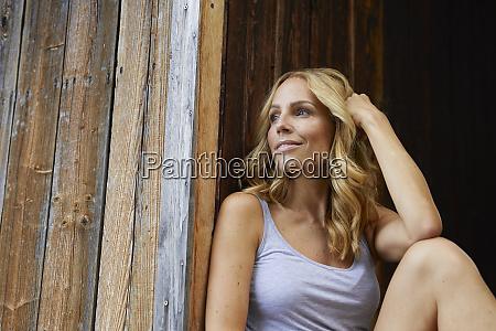 laechelnde blonde frau vor holzhuette