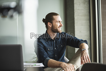 smiling businessman sitting in office looking