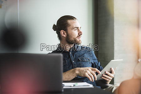 businessman sitting in office with tablet