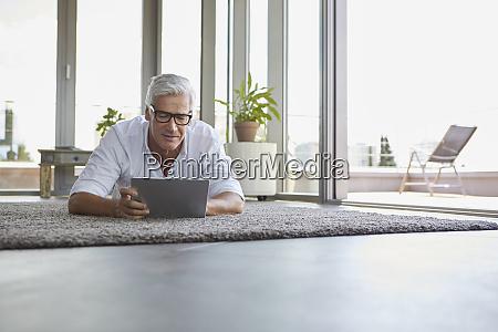 mature man lying on carpet at