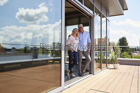 smiling mature couple standing at roof