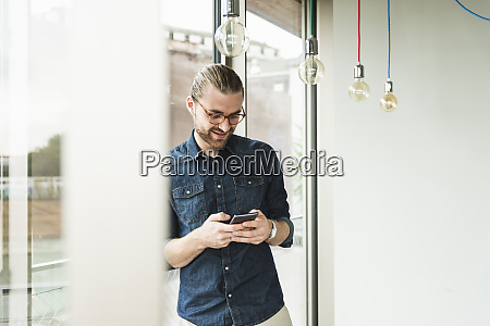 smiling young businessman using cell phone