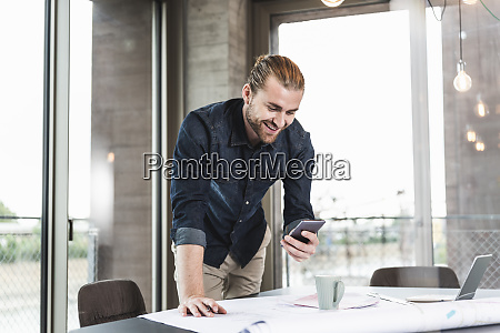 smiling young businessman at desk in