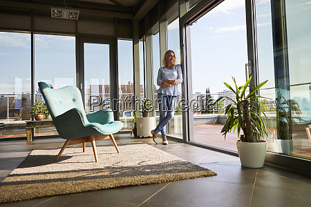 mature woman standing at the window