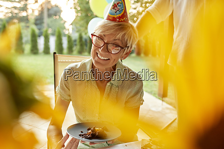smiling mature woman holding plate with
