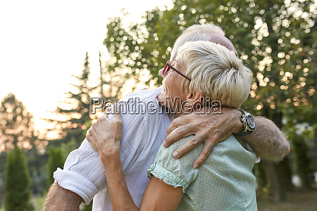 happy senior couple hugging outdoors