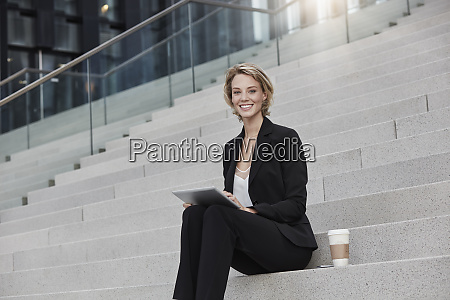 portrait of smiling businesswoman with tablet