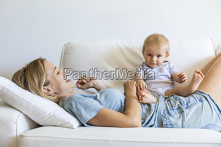 happy mother lying on couch with