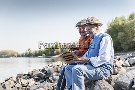 zwei alte freunde sitzen am flussufer