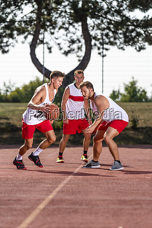 three young men playing basketball on