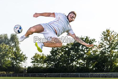 young man kicking soccer ball