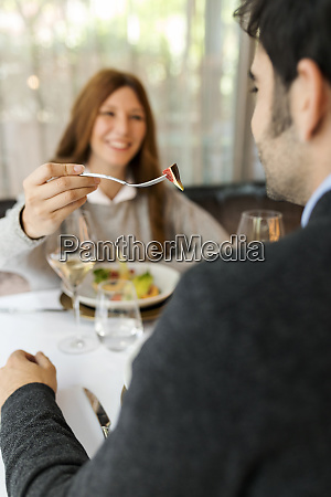 smiling woman letting man taste the