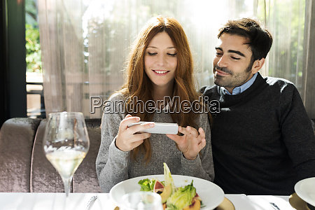 smiling couple using cell phone in