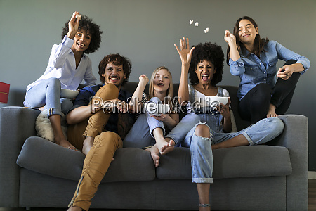 exuberant friends sitting on couch watching
