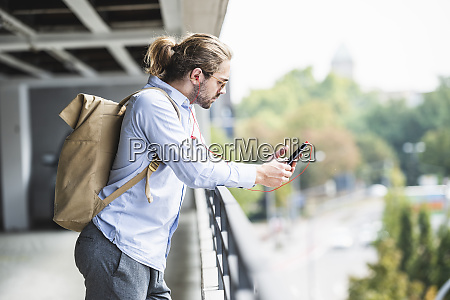 young businessman with backpack standing in