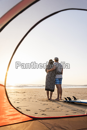 romantisches paar camping am strand umarmt